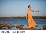 Купить «Молодая девушка в желтом платье стоит на камнях на берегу залива», фото № 12643819, снято 16 августа 2015 г. (c) Литвяк Игорь / Фотобанк Лори