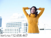 Купить «Happy woman listening music through headphones», фото № 12658467, снято 14 октября 2014 г. (c) Wavebreak Media / Фотобанк Лори