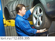 Купить «auto mechanic screwing car wheel by wrench», фото № 12659395, снято 14 апреля 2012 г. (c) Дмитрий Калиновский / Фотобанк Лори