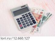 Купить «Российские рубли  калькулятор на столе», фото № 12660127, снято 1 сентября 2015 г. (c) Александр Лычагин / Фотобанк Лори
