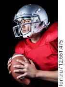 Купить «Determined American football player looking away while holding ball», фото № 12661475, снято 29 мая 2015 г. (c) Wavebreak Media / Фотобанк Лори
