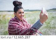 Купить «Beautiful woman using her smartphone», фото № 12665287, снято 20 мая 2015 г. (c) Wavebreak Media / Фотобанк Лори