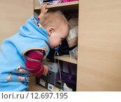 Купить «Мальчик (1 год и 3 месяца) достает вещи из шкафа», эксклюзивное фото № 12697195, снято 7 сентября 2015 г. (c) Вячеслав Палес / Фотобанк Лори