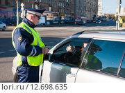 Купить «Сотрудник ДПС проверяет документы у водителя», фото № 12698635, снято 5 октября 2013 г. (c) Михаил Михин / Фотобанк Лори