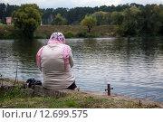 Купить «Православная верующая сидит на берегу реки во время Крестного хода», фото № 12699575, снято 13 сентября 2015 г. (c) Николай Винокуров / Фотобанк Лори