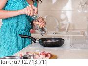 Женщина сыпет перец из мельницы на мясо в сковороде. Стоковое фото, фотограф Вячеслав Николаенко / Фотобанк Лори