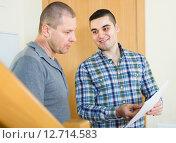Купить «Service employee with tenant at doorway», фото № 12714583, снято 18 августа 2018 г. (c) Яков Филимонов / Фотобанк Лори
