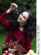 Красивая молодая женщина держит в руках гроздь винограда  и улыбается. Стоковое фото, фотограф Андрей Шарашкин / Фотобанк Лори