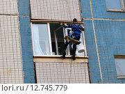 Промышленный альпинист у открытой лоджии панельного многоэтажного дома. Стоковое фото, фотограф Наталья Горкина / Фотобанк Лори