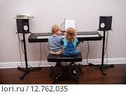 Урок музыки. Девочка и мальчик играют на синтезаторе. (2015 год). Редакционное фото, фотограф Краснощеков Сергей / Фотобанк Лори