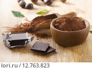 Купить «Chocolate bars and a wooden bowl of cacao powder.», фото № 12763823, снято 8 августа 2015 г. (c) Tatjana Baibakova / Фотобанк Лори