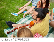 Купить «happy man with friends playing guitar at camping», фото № 12764335, снято 25 июля 2015 г. (c) Syda Productions / Фотобанк Лори
