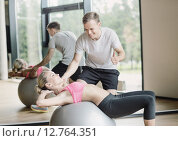 Купить «smiling young woman with personal trainer in gym», фото № 12764351, снято 29 июня 2014 г. (c) Syda Productions / Фотобанк Лори