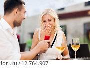 Купить «happy couple with engagement ring and wine at cafe», фото № 12764907, снято 15 июля 2015 г. (c) Syda Productions / Фотобанк Лори