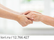 Купить «close up of senior and young woman holding hands», фото № 12766427, снято 10 июля 2015 г. (c) Syda Productions / Фотобанк Лори