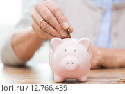 senior woman hand putting money to piggy bank. Стоковое фото, фотограф Syda Productions / Фотобанк Лори