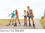 Купить «happy teenagers with rollerblades and longboards», фото № 12769451, снято 10 августа 2014 г. (c) Syda Productions / Фотобанк Лори