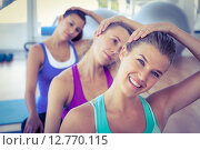 Купить «Portrait of a cheerful woman doing head exercise with friends», фото № 12770115, снято 28 апреля 2015 г. (c) Wavebreak Media / Фотобанк Лори