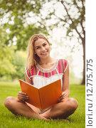 Купить «Portrait of smiling woman holding book while sitting on grass», фото № 12775775, снято 16 июня 2015 г. (c) Wavebreak Media / Фотобанк Лори