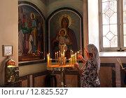 Купить «Женщина ставит свечку в церкви апостола Петра и праведной Тавифы, Яффо, Израиль», фото № 12825527, снято 25 апреля 2015 г. (c) Irina Opachevsky / Фотобанк Лори
