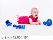 Милая девочка в красном платье лежит на животе среди синих рождественские шаров. Стоковое фото, фотограф Иван Траймак / Фотобанк Лори