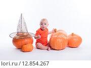 Ребенок в оранжевой футболке в окружении тыкв. Стоковое фото, фотограф Иван Траймак / Фотобанк Лори