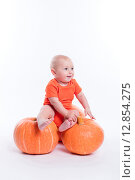 Красивый ребенок в оранжевой футболке сидит на больших тыквах. Стоковое фото, фотограф Иван Траймак / Фотобанк Лори