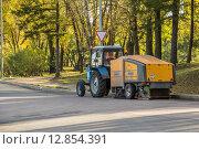 Купить «Трактор МТЗ-80/82 с подметально-уборочной машиной Broddway Wasa 300 подметает опавшие листья осенним солнечным утром», фото № 12854391, снято 6 октября 2015 г. (c) Andrea Rudi / Фотобанк Лори