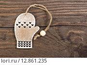 Купить «Деревянное елочное рождественское украшение в виде варежки на деревянном фоне», фото № 12861235, снято 10 октября 2015 г. (c) Наталия Пыжова / Фотобанк Лори