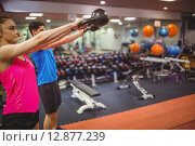 Купить «Fit couple working out in weights room», фото № 12877239, снято 16 июля 2015 г. (c) Wavebreak Media / Фотобанк Лори