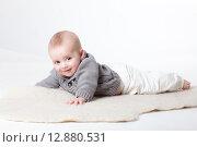 Купить «Малыш улыбается лежа на животе в теплом свитере», фото № 12880531, снято 19 ноября 2018 г. (c) Efanov Aleksey / Фотобанк Лори