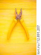 Купить «Old pliers on the yellow background», фото № 12891207, снято 21 февраля 2019 г. (c) PantherMedia / Фотобанк Лори