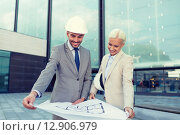 Купить «smiling businessmen with blueprint and helmets», фото № 12906979, снято 19 августа 2014 г. (c) Syda Productions / Фотобанк Лори