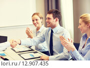 Купить «smiling business team shaking hands in office», фото № 12907435, снято 25 октября 2014 г. (c) Syda Productions / Фотобанк Лори