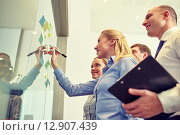 Купить «smiling business people with marker and stickers», фото № 12907439, снято 25 октября 2014 г. (c) Syda Productions / Фотобанк Лори