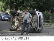 Дорожно-транспортное происшествие. Водитель стоит около перевернутого набок автомобиля (2009 год). Редакционное фото, фотограф Дмитрий Пискунов / Фотобанк Лори