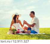 Купить «smiling couple with small red gift box on picnic», фото № 12911327, снято 23 июля 2014 г. (c) Syda Productions / Фотобанк Лори