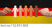 hands with paper people pictogram over german flag. Стоковое фото, фотограф Syda Productions / Фотобанк Лори