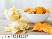 Купить «close up of potato crisps and nachos in glass bowl», фото № 12912327, снято 22 мая 2015 г. (c) Syda Productions / Фотобанк Лори
