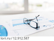 close up of eyeglasses and files on office table. Стоковое фото, фотограф Syda Productions / Фотобанк Лори