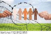 Купить «hands holding people pictogram over barb wire», фото № 12912951, снято 22 апреля 2019 г. (c) Syda Productions / Фотобанк Лори