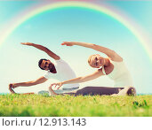 Купить «happy couple stretching and doing yoga exercises», фото № 12913143, снято 6 августа 2014 г. (c) Syda Productions / Фотобанк Лори