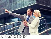 Купить «smiling businessmen with tablet pc outdoors», фото № 12913151, снято 19 августа 2014 г. (c) Syda Productions / Фотобанк Лори