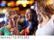 Купить «happy young women singing karaoke in night club», фото № 12913283, снято 20 октября 2014 г. (c) Syda Productions / Фотобанк Лори