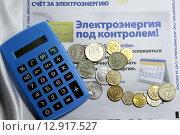Калькулятор и мелкие монеты на фоне платежки за свет. Редакционное фото, фотограф Асия Абубакрова / Фотобанк Лори