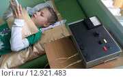 Девочка лежит на кушетке и играет с телефоном во время процедуры электрофореза в детской поликлинике (2015 год). Редакционное видео, видеограф Кекяляйнен Андрей / Фотобанк Лори