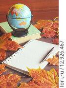Осенний натюрморт с кленовыми листьями, глобусом и блокнотом на столе. Стоковое фото, фотограф Зезелина Марина / Фотобанк Лори
