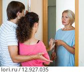 Купить «Young spouses receiving irritated senior neighbor at doorway», фото № 12927035, снято 17 августа 2018 г. (c) Яков Филимонов / Фотобанк Лори