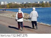 Купить «Осень в Коломенском. Две пожилые женщины прогуливаются по набережной Москва-реки с палками для скандинавской хотьбы», фото № 12947275, снято 21 октября 2015 г. (c) Natalya Sidorova / Фотобанк Лори