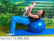 Мама с маленьким ребенком делают гимнастику (2015 год). Редакционное фото, фотограф Евгений Чернышов / Фотобанк Лори